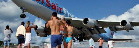 """Пляж """"Махо Бич"""", где находится известный пляж. Видео, как людей снесло реактивными двигателям авиалайнера. Самолеты пролетают прямо над головой. Всемирно известный пляж """"Махо Бич"""" расположенный на острове Сен Мартен, стал популярным благодаря близости заходящих на посадку пассажирских самолетов. На какой высоте пролетают самолеты на пляже Махо, где находится известный пляж, в чем его опасность и другие интересные факты о пляже Махо (Maho Beach) в нашей статье"""
